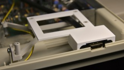The holder frame (white) sits within the frame of the GOEX drive (grey) and does not need any screws.